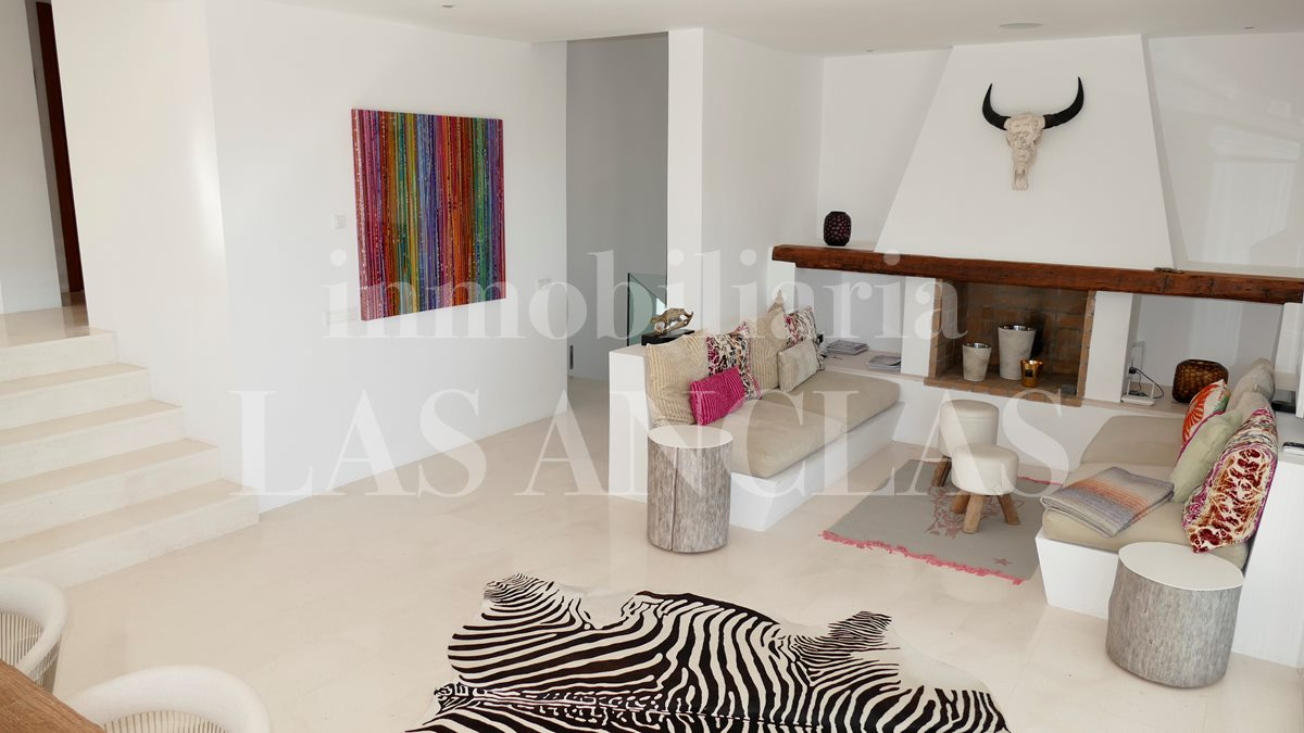 Living room with bricked sofas and fireplace - luxury villa in Jesús Ibiza for sale