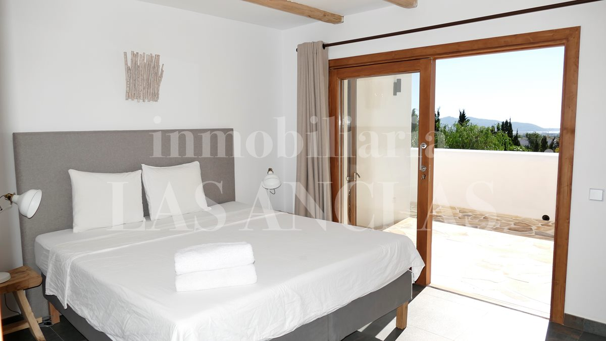Bedroom with large glass doors gains access to the terrace with sea views - luxury villa between Ibiza & San José for sale